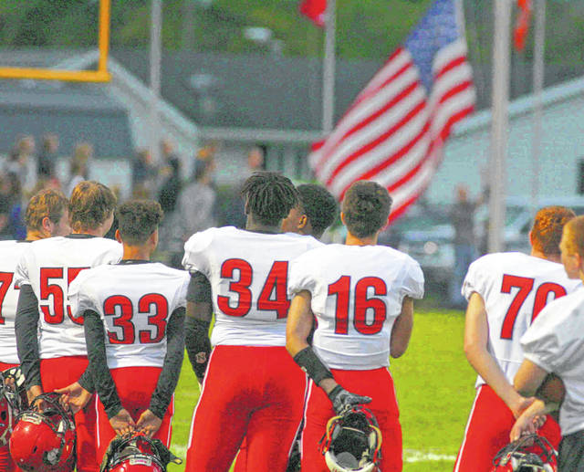 The Shawnee players stand for the national anthem before Friday night's game in Ottawa.