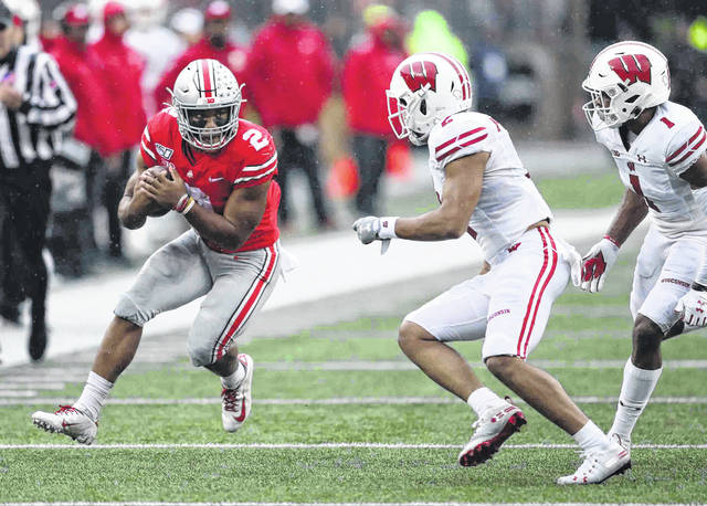 Ohio State running back J.K. Dobbins protects the ball as he is about to get hit by Wisconsin's Reggie Pearson (2) and Faion Hicks (1) during Saturday's game at Ohio Stadium in Columbus.