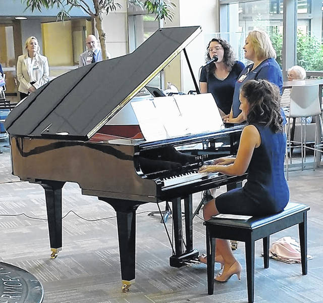 Mercy Health-Lima market president Ronda Lehman plays the piano in the St. Rita's lobby. Nursing manager Tammy Kill and Hannah Salsbury performed vocals.