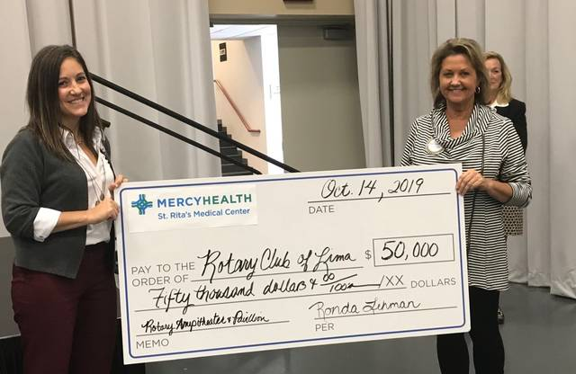 Ronda Lehman (left), president of Mercy Health's Lima market and St. Rita's Medical Center, presents a $50,000 check to Tracie Sanchez (right) during the Lima Rotary Club's meeting on Monday.