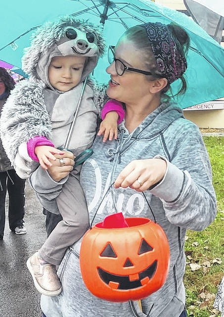 Kristan Horstman and her daughter, Pearl, pick up some treats at the annual Safety City Trick or Treat Saturday.