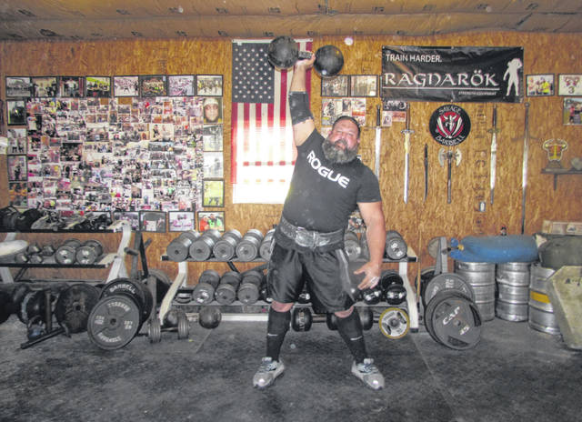 Steve Schmidt, of Columbus Grove, trains for upcoming Strongman competitions using a 172-pound Thomas Inch dumbbell in his home gym.