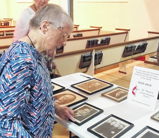 Meredith Bradshaw looks over historical pictures after Sunday's 100th anniversary service at St. Mark's United Methodist Church.