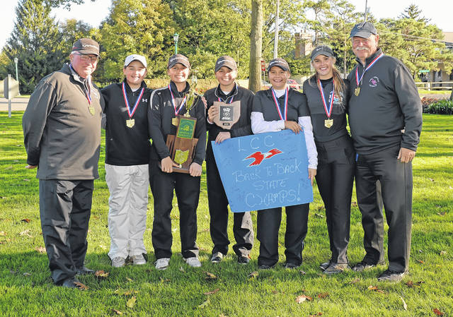 From left, Assistant Coach Pete Hubbell, Bridget Mulcahy, Erin Mulcahy, Mary Kelly Mulcahy, Carlie VanMeter, Emma Mayers, and Head Coach Daniel Reinieke are all smiles after Lima Central Catholic won its second straight girls Division II state golf championship on The Gray Course at The Ohio State University in Columbus.