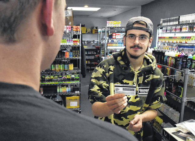 Max Santiago, an employee at DG Essentials vaping store on Elida Road in Lima, checks a customer's ID before selling vaping products at the store. DG Essentials started checking ID's and only selling tobacco products to 21-year-olds starting Oct. 1. Statewide, you must be 21 to buy tobacco or vaping products starting Thursday.