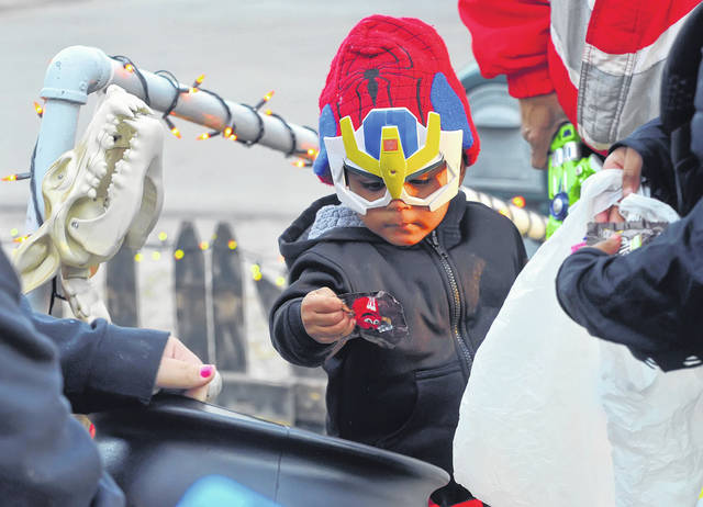 Dareal Scales, 2, collects candy dressed as Spiderman during Lima's trick or treat.