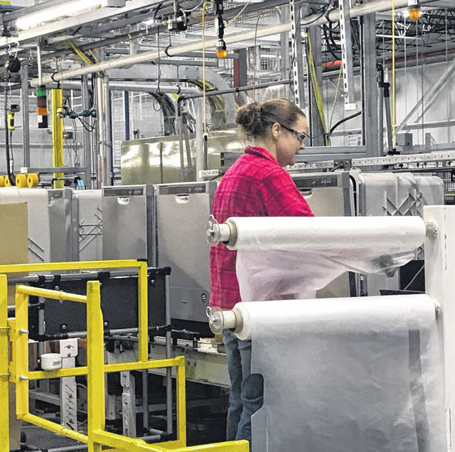 An assembler at Whirlpool's Findlay production plant wraps and packs appliances that are ready for shipping. Artificial intelligence can spot defects on products before they get too far along the assembly line.