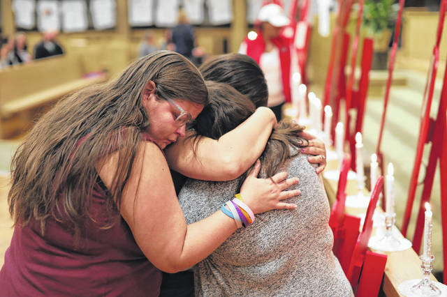 Carla Lukle, the aunt of victim 18 month-old Kadon Luke, hugs her family tight after Crossroads Crisis Center 25th	Annual Candleight Vigil held at the Trinity United Methodist Church in Lima on Thursday evening. Amanda Wilson Photo | The Lima News