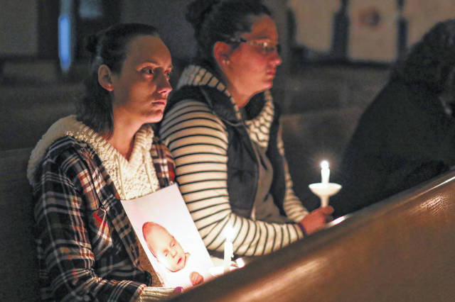 Savanna Cox of St. Marys (left) holds the photo of her sister, 9 month-old victim Jasmine Fricke-Simpkins, and sits with her friend Krista Prater during Crossroads Crisis Center's 25th Annual Candleight Vigil held at the Trinity United Methodist Church in Lima on Thursday evening. Amanda Wilson Photo | The Lima News