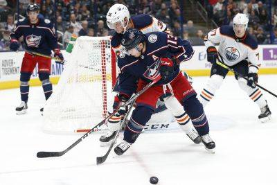 Edmonton's Joel Persson, top, knocks the puck away from the Blue Jackets' Cam Atkinson during  Wednesday night's game in Columbus. (AP photo)