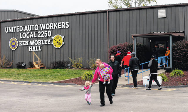 """United Auto Worker Lindsey Higgins, exits the the UAW Local 2250 Ken Worley Hall with her two children after voting on the offer made to union workers by General Motors on Thursday, Oct. 24, 2019, in Wentzville, Mo. """"I don't feel great about the contract but I have these two to think about. I can't keep striking. I've got to keep a roof over their head,"""" said Higgins. UAW workers have been on strike since Sept. 16."""