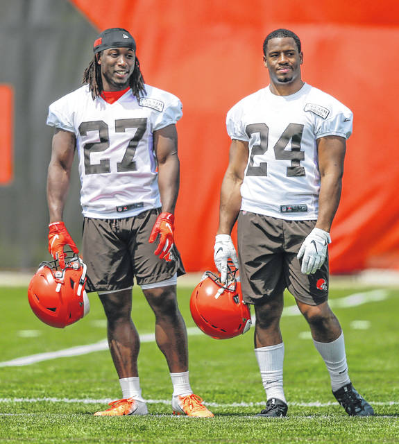 FILE - In this May 15, 2019, file photo, Cleveland Browns' Kareem Hunt (27) and Nick Chubb (24) talk during an NFL football organized team activity session at the team's training facility in Berea, Ohio. With Kareem Hunt returning from his eight-game NFL suspension to join Nick Chubb in Cleveland's backfield, the Browns (3-6) have a dynamic duo that will test opposing defenses through the air and on the ground. In Sunday's 19-16 win over Buffalo, the Hunt-Chubb tandem combined for 147 yards rushing and 49 receiving while helping the Browns snap a four-game losing streak that halted a season shaped by high expectations from dissolving into another mess. (AP Photo/Ron Schwane, File)