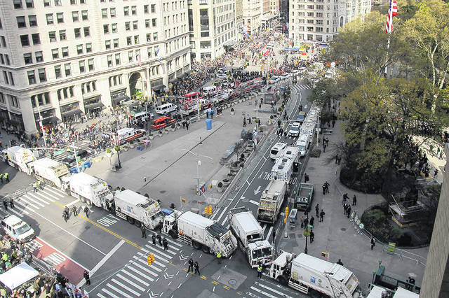 "On Monday, sanitation and other utility trucks block off the streets around Madison Square Park as crowds and protesters gather for President Donald Trump's address to kick off the New York City's 100th annual Veterans Day parade in New York. The Associated Press reported on stories circulating online incorrectly asserting that sanitation trucks surrounding Madison Square in New York were lined up to protect Trump against booing protesters. Officials with the New York City Police Department and the Department of Sanitation confirmed that sanitation trucks are often used for security at big events. They are ""part of our counterterrorism overlay, not unique to this visit,"" Lt. Eugene Whyte, of the NYPD's public information office, told the AP."