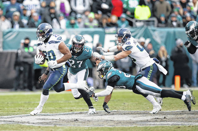 Seattle Seahawks' Rashaad Penny (20) runs for a touchdown past Philadelphia Eagles' Malcolm Jenkins (27) and Rodney McLeod (23) during the second half of an NFL football game, Sunday, Nov. 24, 2019, in Philadelphia. (AP Photo/Michael Perez)
