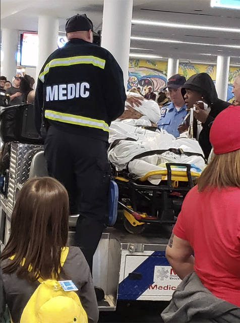 This photo provided by Eric Linne shows medics attending to a woman after giving birth on the plane at at Charlotte Douglas International Airport, Wednesday, Nov. 27, 2019 in Charlotte, N.C. News outlets report Nereida Araujo went into labor Wednesday on a flight from Tampa, Florida, to Charlotte, N.C.   American Airlines spokeswoman Crystal Byrd says the flight crew radioed medics who helped deliver the baby on the plane once it landed. Passenger Eric Linne says on Facebook that a crowd burst into spontaneous applause when Araujo and the baby were brought off the plane.   (Eric Linne via AP)