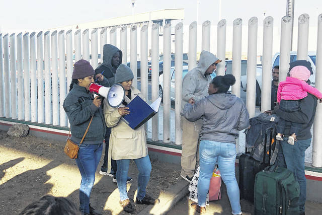 In this Nov. 12, 2019, photo, volunteers call names of people on a waiting list trying to obtain asylum in the United States along the U.S.-Mexico border in Tijuana, Mexico. The U.S. has sent a Honduran migrant back to Guatemala in a move that marked a new phase of President Donald Trump's immigration crackdown.