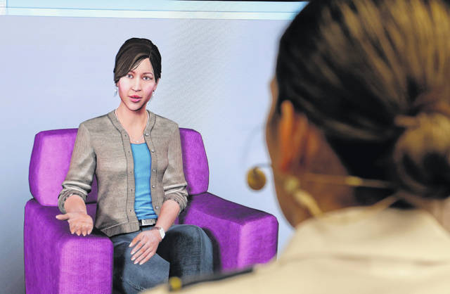 "In this file photo from May 2, 2019, Cadet Cheyenne Quilter works with a virtual reality character named ""Ellie"" at the U.S. Military Academy at West Point, N.Y. Artificial intelligence is spreading into health care, often as software or a computer program capable of learning from large amounts of data and making predictions to guide care or help patients."