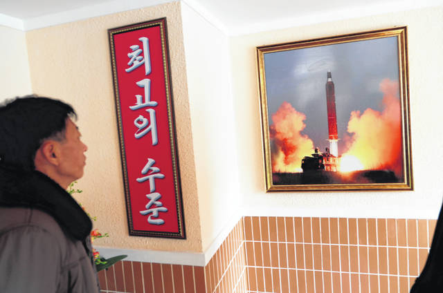 """In this Nov. 26, 2019, photo, a man looks at a photo of the launch of a missile hanging on the wall of a factory workers' dormitory in Pyongyang, North Korea. Fears rise that North Korea's year-end deadline to the U.S. to offer some new initiative to the nuclear-standoff means that nearly two years of head-spinning diplomatic engagement might be in danger of falling apart. Sign in Korean reads; """"Highest level."""""""