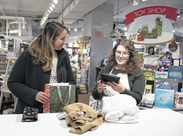 Halle Wagner, right, helps Katherine Gailey return items she purchased online from Everlane on Nov. 12 at a Paper Source store in Chicago. Paper Source works with a company called Happy Returns to process returns for other online brands.