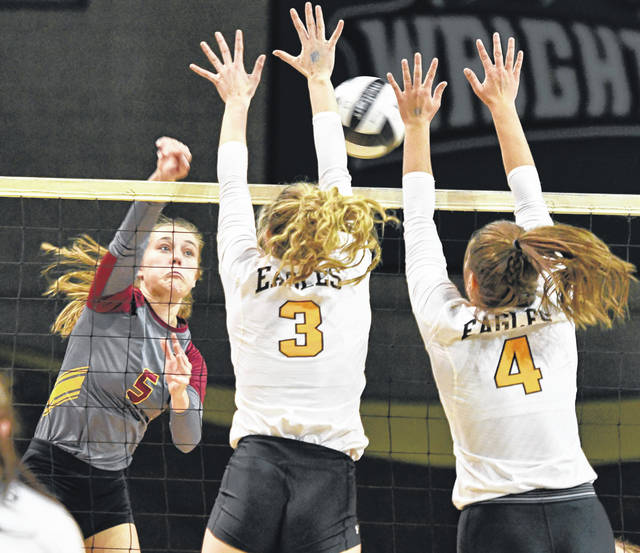 New Bremen's Josie Reinhart (5), sends a spike at Monroeville's Kelse Palmer, center, and Maura Brown during a Division IV state semifinal on Friday at Wright State University's Nutter Center in Fairborn.