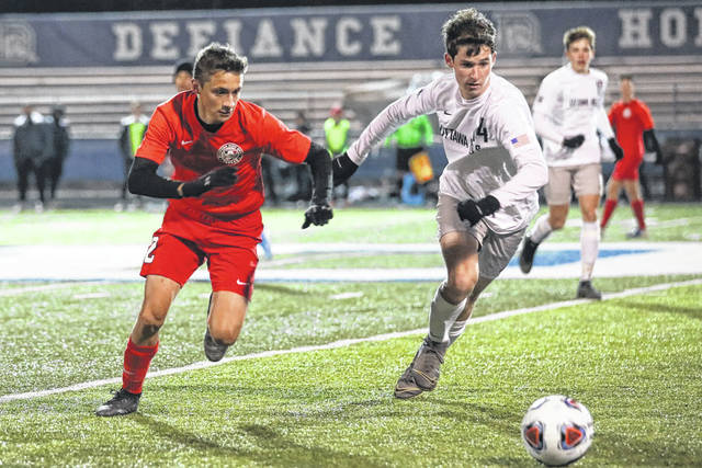Bluffton's Collin Oglesbee and Ottawa Hills' Jack Silk race to gain control of the ball during Saturday night's Division III regional final at Defiance High School.