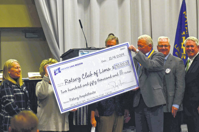 Members of the Greater Lima Region Inc. board playfully raise the cardboard check to obscure Tracie Sanchez during the check presentation.