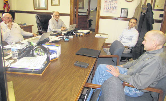 From left are Putnam County Commissioners John Schlumbohm and Vincent Schroeder talking with Dylan Borchers, attorney representing Avangrid, and Jeff Reinkemeyer, Eastern Renewables Development director, about a solar farm proposal in Miller City.