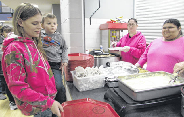 Justine Dickey, Leipsic, and her son, Gage Kuhbander, 4, Leipsic, are served a Thanksgiving meal by volunteers from left Jolynn Hernandez and Michaela Flores Thursday night at Leipsic Community Center.