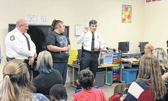 In addition to presenting a plaque to Great Day Academy in honor of Matthew Converse, the Lima Police Department gave Converse's mother, Stephanie Berna (center), a Challenge Coin.