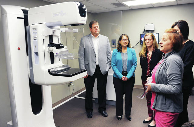 Mammography Technologist Tina Bryant, far right, of Sidney, talks about one of the new 3D mammography imaging machines, far left, that Wilson Health recently purchased. Listening to her are, left to right, Vice President and General Manager of Honda of America technology division Paul Dentinger, of Anna, Vice President and General Manager of purchasing at Honda of America Pam Heminger, of Dublin, and Honda Planning and Communication Coordinator Carla Greene, of Bellefontaine. The Honda representatives were taken on a tour, Thursday, Nov. 21, of the new mammography technology their company helped Wilson Health purchase.