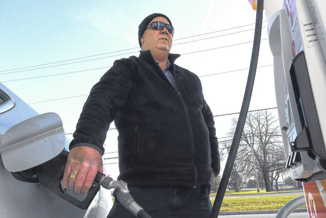 Dean Bidlack, of Continental, fills up his gas tank for the holiday at a Circle K on North West Street in Lima.