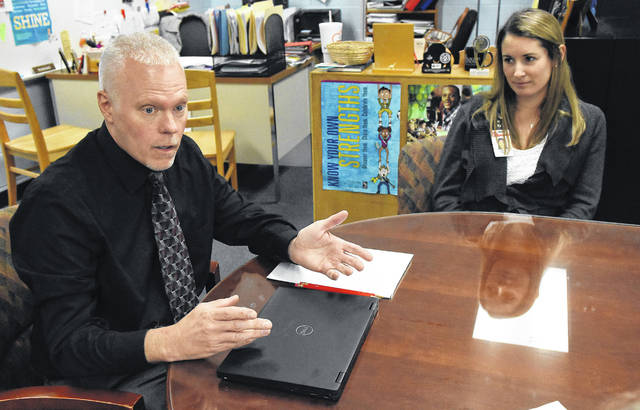 Brian Wischmeyer, left, the special education director for Lima schools, works on an individualized education plan with Katie Baker, a psychologist with the district.