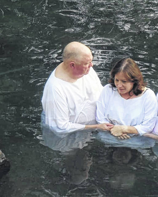 The Rev. Duane Kemerley, left, pastor of Pandora and Riley Creek United Methodist Churches, provides a baptismal renewal in the Jordan River to a woman. He visited the Holy Land recently.