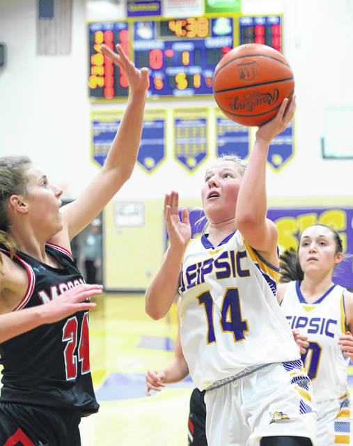 Leipsic's Whitney Langhals shoots against McComb's Malorie Schroeder during Wednesday's game at Leipsic High School. Richard Parrish | The Lima News