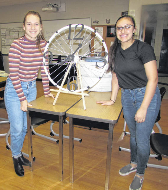 From left are Leipsic High School seniors Aubree Schroeder and Schilene Giron with a repurposed clock they made using a bicycle rim.