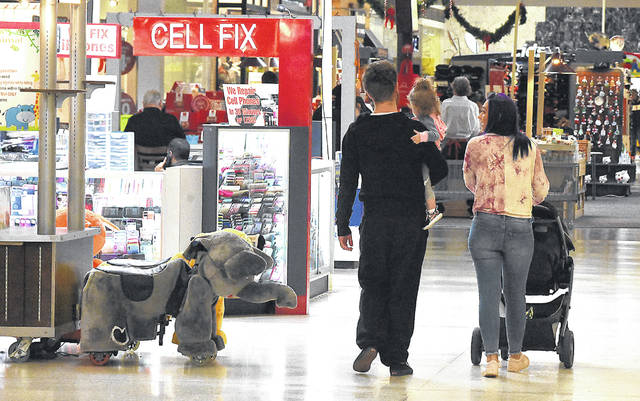 Jana Kramp, far right, walks through the Lima Mall with her daughter, Myla, 1, and Mason Risner while Christmas shopping on Thursday. Many consumers started their holiday shopping earlier this year, especially with Thanksgiving falling six days later than it did last year.