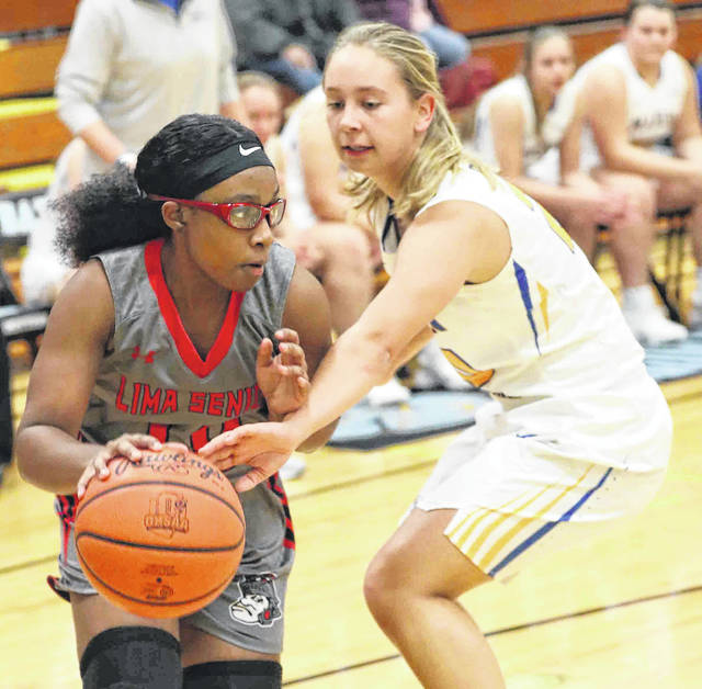 Marion Local's Olivia Demange guards Lima Senior's Nakiya Sigman during Friday night's Kewpee Tip-Off Tournament at Bath.