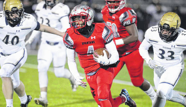 Lima Senior's Cecil Benton Jr. is pursued by John Spidel (40) and Chris Lash (33) of Toledo St. John's during Friday night's game at Spartan Stadium.