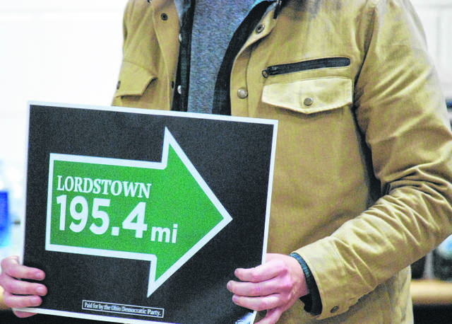 A person picketing holds a sign referencing Lordstown.