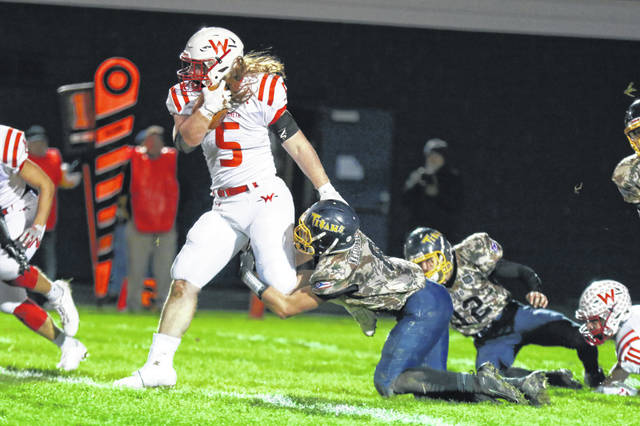 Ottawa-Glandorf's Rodney Meyer hangs on to Wapakoneta's Evan Kaeck during Friday night's game in Ottawa.