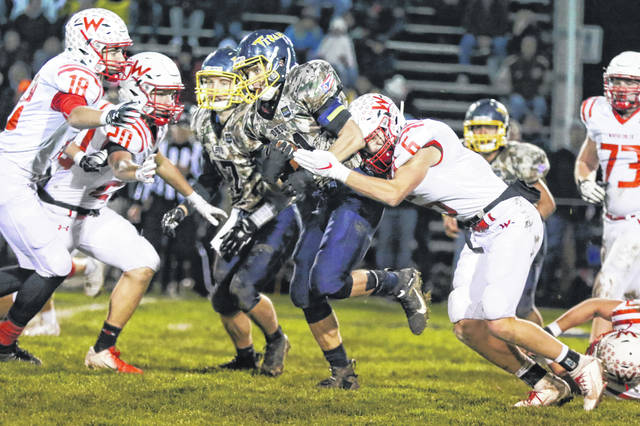 Ottawa-Glandorf's Jacob Balbaugh fights for yardage against Wapakoneta's Isaac Meeks (6) during Friday night's game in Ottawa.