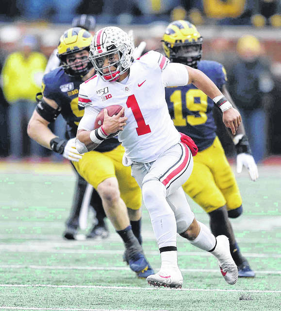 Ohio State's is pursued by Michigan's Aidan Hutchinson, left, and Kwity Paye during Saturday's game in Ann Arbor, Mich.
