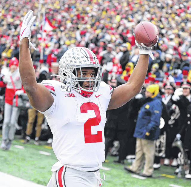 Ohio State running back J.K. Dobbins forms the letter H from the O-H-I-O chant after scoring one of his four touchdowns Saturday during the Buckeyes' 56-27 victory against Michigan.