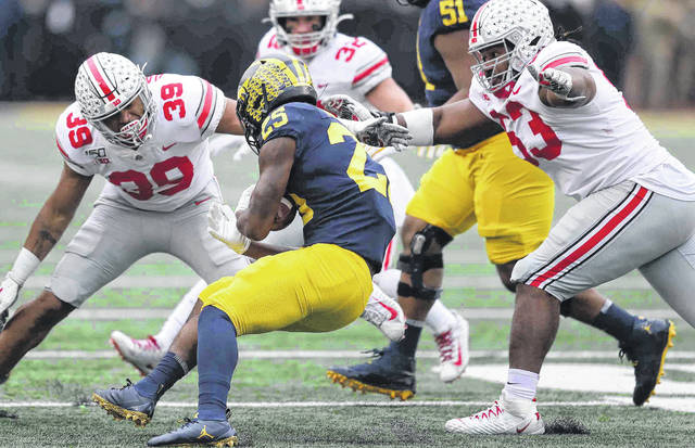 Ohio State's Malik Harrision, left, and Davon Hamilton bottle up Michigan's Hassan Haskins during Saturday's game in Ann Arbor, Mich.