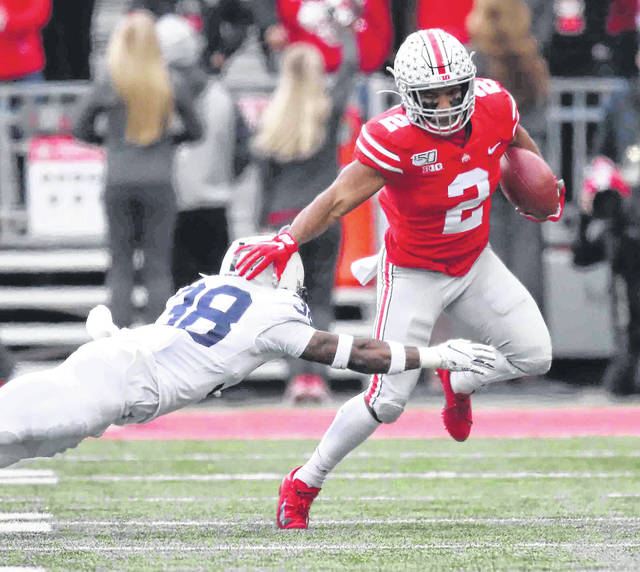 Ohio State's J.K. Dobbins fends off Penn State's Lamont Wade during Saturday's game at Ohio Stadium in Columbus.