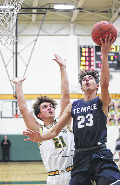 Temple Christian's Preston Patrick puts up a shot against Ottoville's Drew Fisher during Friday night's game in the L.W. Heckman Gymnasium in Ottoville.