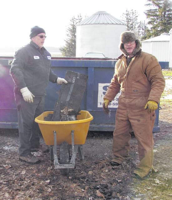 Habitat for Humanity of Putnam County volunteers from left Gary Louiselle and Tom Wehri discard old roof material.