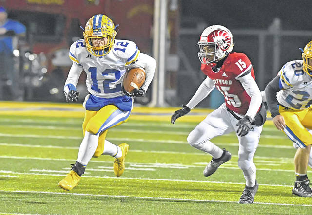 St. Marys' Ty Howell tries to get away from Trotwood-Madison's Kwaelinn Kirk during Friday night's Division III regional semifinal at Sidney Memorial Stadium.