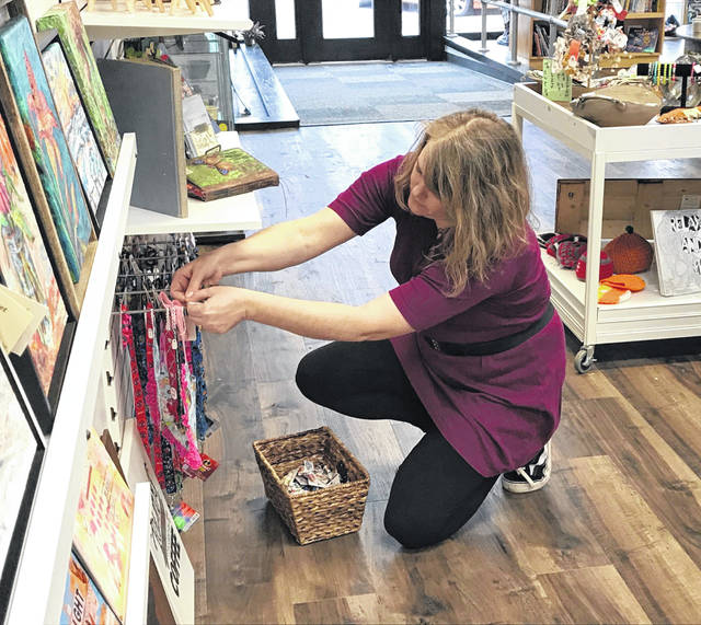 Jennifer Brogee, co-owner of Shop for Good gifts boutique on North Main Street, adjusts a display ahead of Thanksgiving Day. The boutique was open Black Friday and Small Business Saturday.