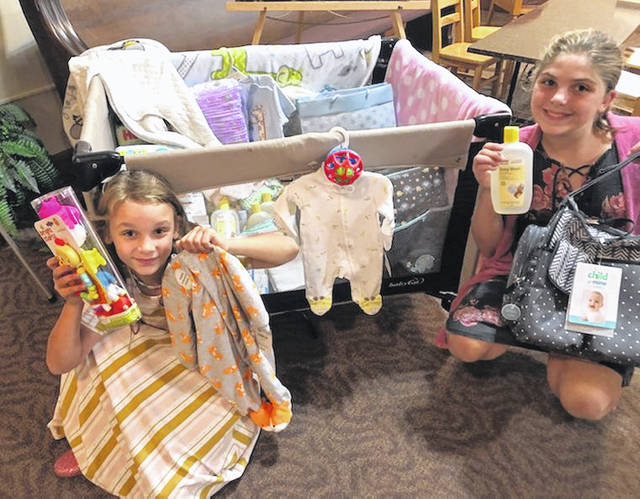 Sunday school children also helped in the ministry by donating small baby toys as one of their service projects. Elora and Ashlynn are shown with all of the donations.